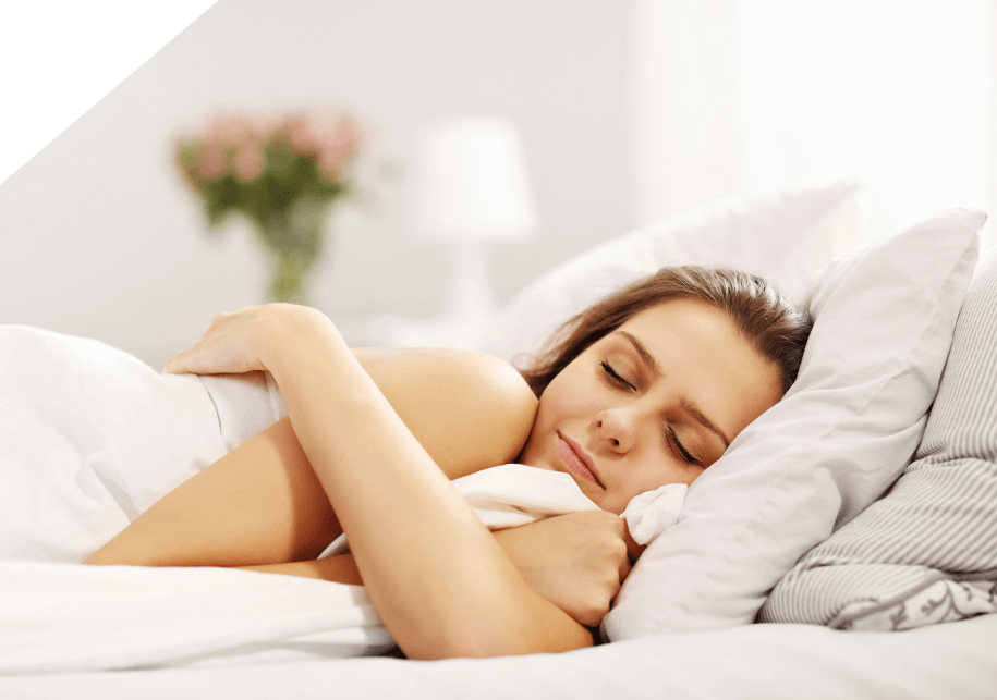 Female sleeping on side on white sheets with a partial smile on her face