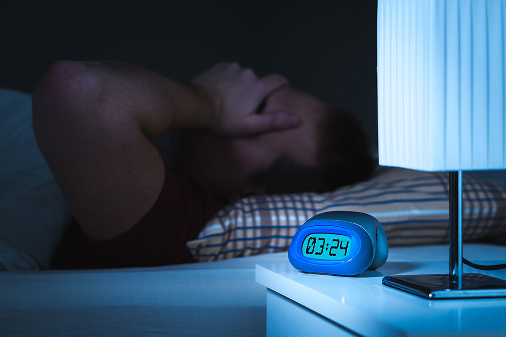 Overweight man having trouble sleeping.
